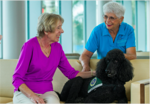 Volunteers Betty Wiese, left, and Anne Misek and therapy dog Casey
