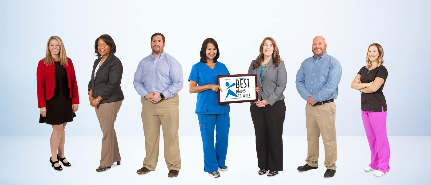 "Staff with ""Best Place to Work"" sign"
